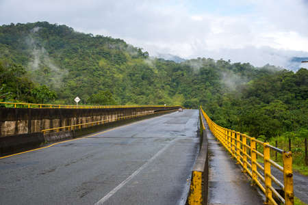 wet highway bridge between mountains with abundant vegetation. Colombia .