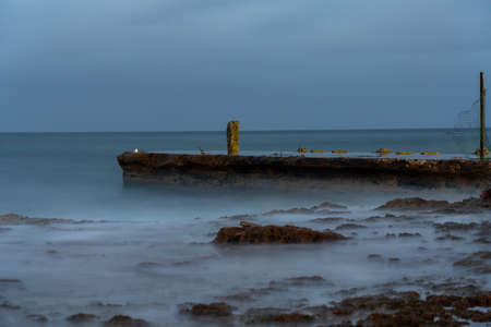 Low exposure photo of a small pier at dusk on a Havana coast. Cuba
