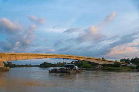 Car and passenger ferry across a river with bridge under construction in the background at sunset. Cordova. Colombia. 11 of December 2019. 報道画像