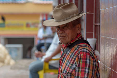 Old man with hat sitting in a market square in a rural town. Santander Colombia. August 1, 2019.