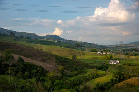 Country landscape of farms and hills with power lines. Colombia