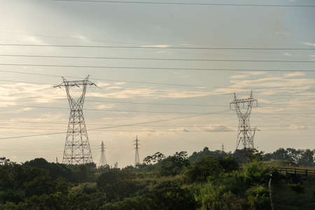 High voltage electricity pylons in a Colombian country landscape in the evening light.