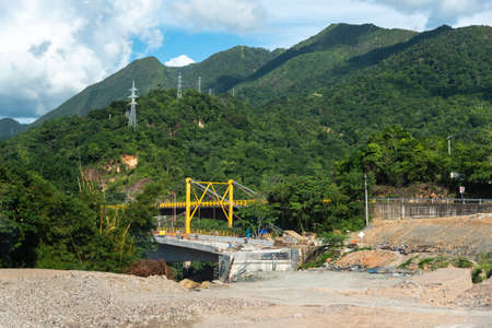 Construction of a bridge for a highway in the Colombian countryside with high voltage current towers on the mountain. 写真素材