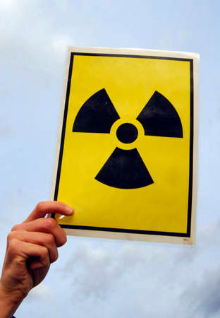 hand holding warning sign for radioactive material