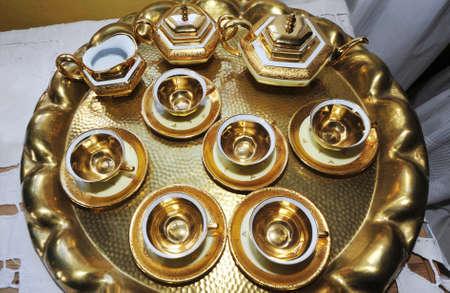 serving a golden coffee set