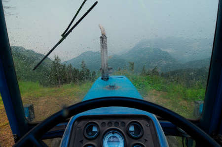 sitting in a tractor during rain shower Stock Photo