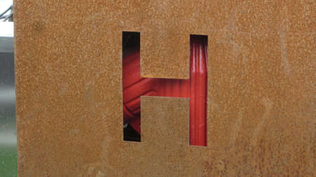 The letter 'H' on a rusty material