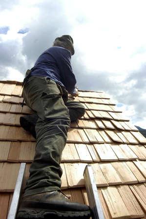 Farmer repairing roof of alpine hut