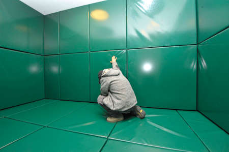 Man kneeling in green padded cell