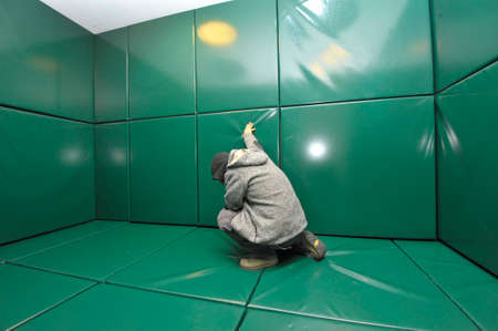 Man kneeling in green padded cell Stock Photo