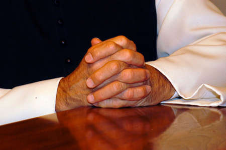 priest folding his hands for prayer