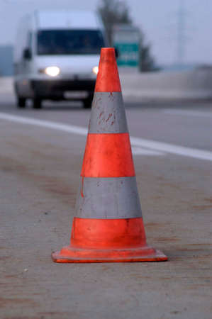 Road safety: traffic cone in front and car headlights in the back