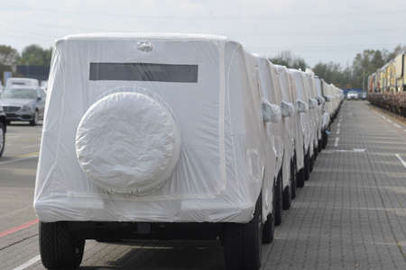 Off-road vehicles covered with white tarp Фото со стока