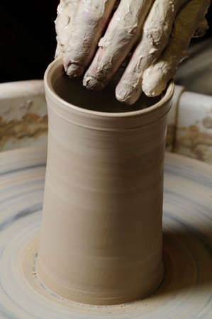 making pottery with hand on pottery wheel