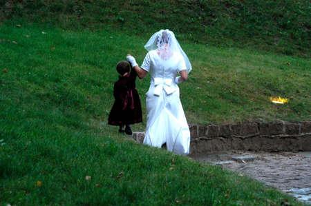 bride in wedding dress with child