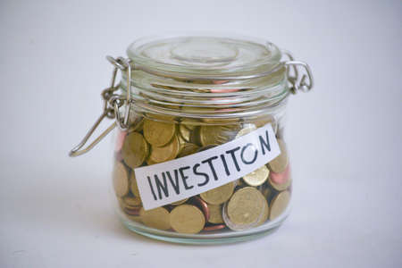 jar with coins and label 'Investition' (investment), symbol for economic upturn