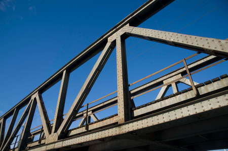 a truss bridge with clear blue sky in the background