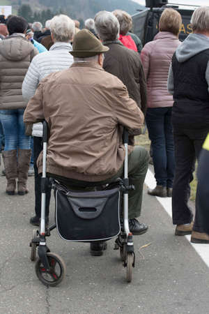 rollator as walking aid for old man in a group of people