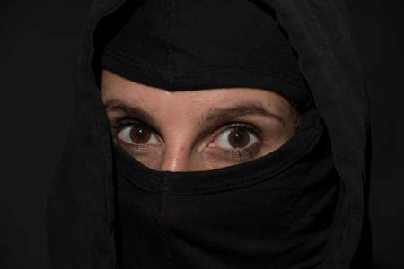 eyes of a young woman, face veiled in black clothing Reklamní fotografie