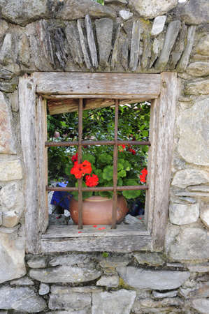garden fence with stone wall and a pot with a flower