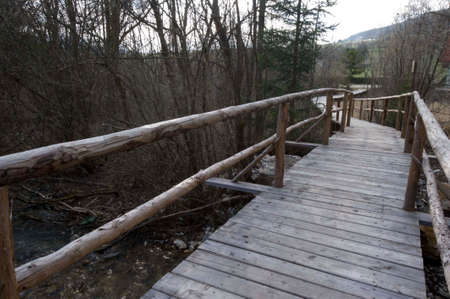 wooden bridge as a footpath that leads over a river