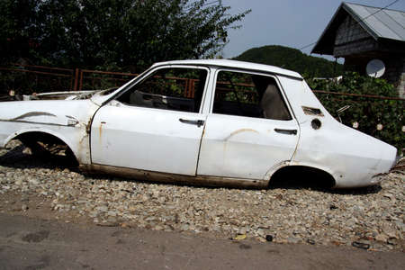 white rusty car without tyres, hood and engine block before scrapping Фото со стока