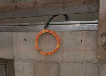orange power cable hanging rolled up at a wall at the construction site