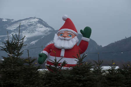 big Santa Claus decoration at a christmas tree sell, snowy mountain in the back