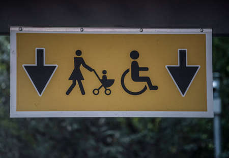 sign with parent with stroller and person in wheelchair, disability in the family