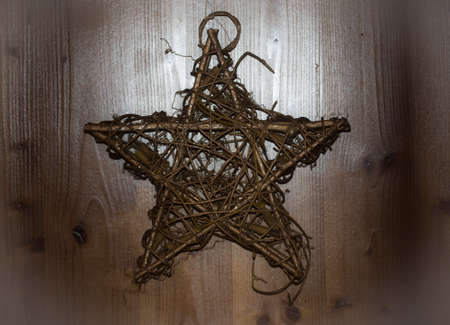 a christmas star made of straw hanging on a door