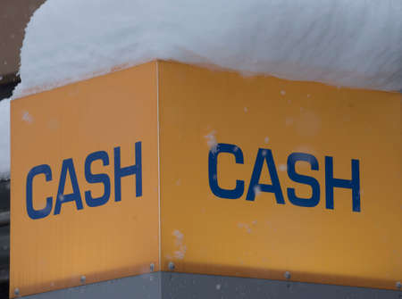 yellow cash sign covered in snow, on a snowy winter day