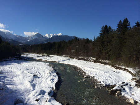 river in the winter, blue sky, snowy mountains in the back
