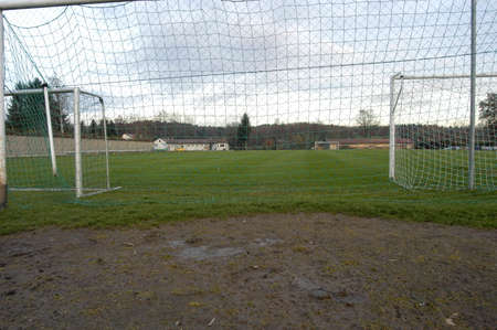 football or soccer field with green grass, goals and mud Imagens