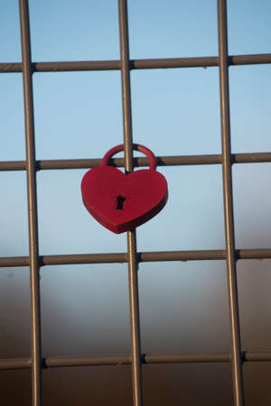 red heart shaped lock on a fence, symbol of love