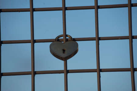 heart shaped lock or love lock on a fence, symbol for love