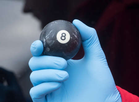 playing a game of billiard, person holding the black number eight ball in their hand