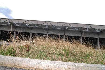 an industrial concrete building, covered parking garage and grass Stockfoto