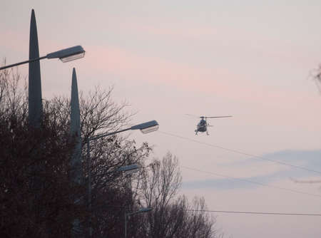 street light at sunset, with helicopter flying in the background Foto de archivo