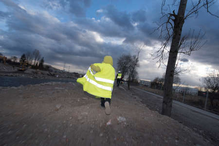 child wearing a yellow warning vest running in the twilight