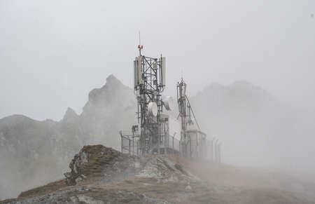 mobile network antennas on top of a mountain, foggy background
