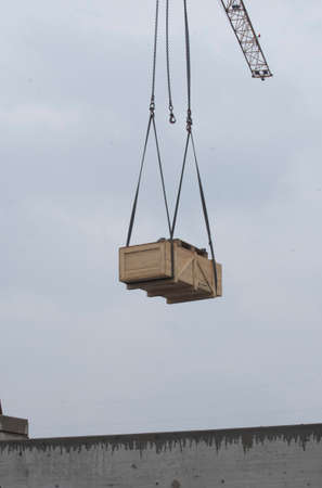 a crane lifts a wooden crate in gray sky, industrial goods transport Imagens