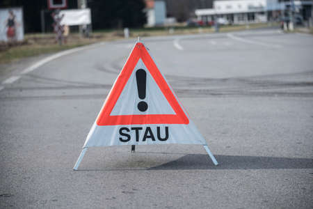 red and white warning triangle congestion (Stau) sign, standing on the road