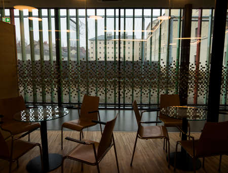 chairs and glass tables, inside a visitor center of a prison