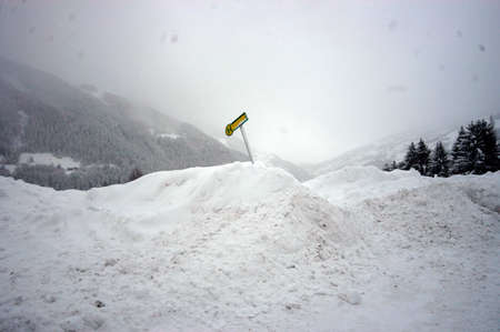 bus stop traffic sign in europe, green and yellow sign covered in snow in winter 写真素材