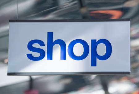 shop sign on a window, white sign with blue letters