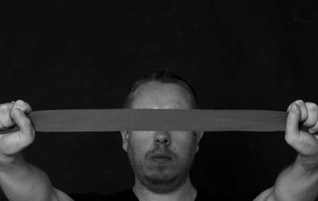 man holding a ribbon in front of his head, covering his eyes, black and white, depression symbol Stock Photo
