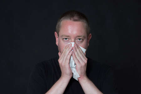 man blows his nose with a handkerchief, having a cold, black background Stok Fotoğraf