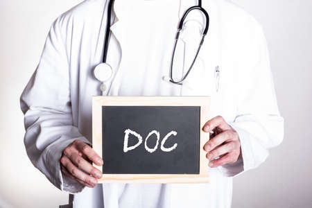 doctor in white shirt wearing a stethoscope around his neck holding a small blackboard that says DOC Banque d'images