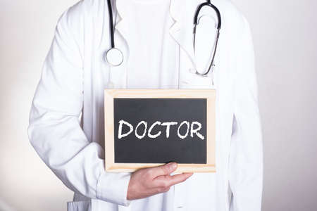 doctor in white shirt wearing a stethoscope around his neck holding a small blackboard that says DOCTOR