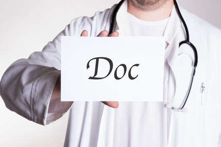 doctor in white shirt wearing a stethoscope around his neck holding a sign that says DOC